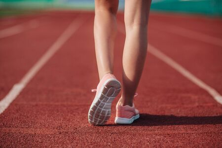 Sport. Female legs in pink sneakers on running track stadium. Close-up on sports shoes of a running woman. Concept run.