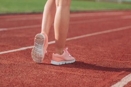 Girl legs in sport shoes standing on a running track with stadium stands. back view. close up.