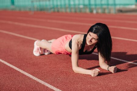 Young slim attractive brunette woman in pink shorts and black top doing plank exercise at outdoor stadium, core training and fitness concept, sun flare.