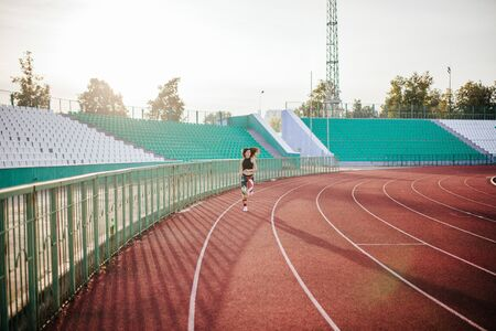 Sport. Athletic young brunette woman in pink sneakers, leggings and top run on running track stadium at sunset. her hair is developing. Concept run. concept of a healthy lifestyle.