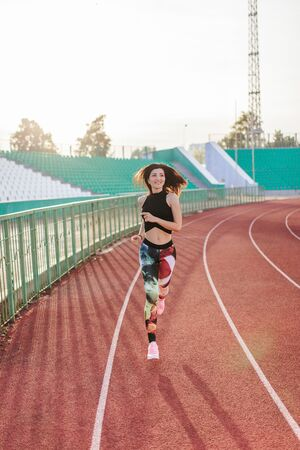 Sport. Athletic young brunette woman in pink sneakers, leggings and top run on running track stadium at sunset. her hair is developing. Concept run. concept of a healthy lifestyle. 스톡 콘텐츠