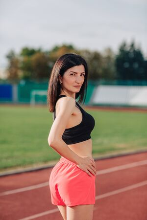 Portrait of stylish beautiful brunette woman with a perfect figure in pink shorts and top posing for the camera on running track at the stadium 스톡 콘텐츠