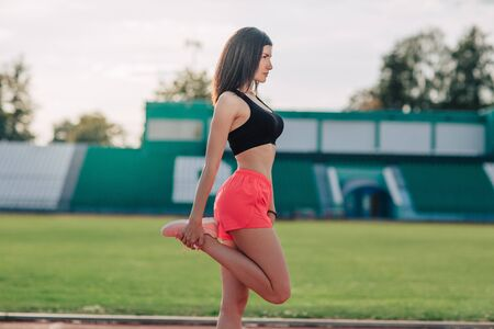 Young brunette woman athlete in pink shorts and top on stadium sporty lifestyle standing stretching leg side view. 스톡 콘텐츠