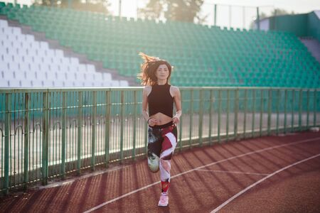 Sport. Athletic young brunette woman in pink sneakers, leggings and top run on running track stadium at sunset. her hair is developing. Concept run. concept of a healthy lifestyle 스톡 콘텐츠