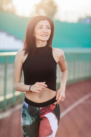 Portrait of Athletic young brunette woman in pink sneakers, leggings and top run on running track stadium at sunset. her hair is developing. Concept run. concept of a healthy lifestyle 스톡 콘텐츠