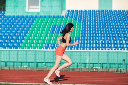 Girl running track on stadium. Real side view of young woman in pink shorts and tank top and pink sneakers. Outdoors, sport.