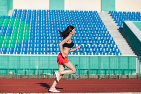 Girl running track on stadium. Real side view of young woman in pink shorts and tank top and pink sneakers. Outdoors, sport