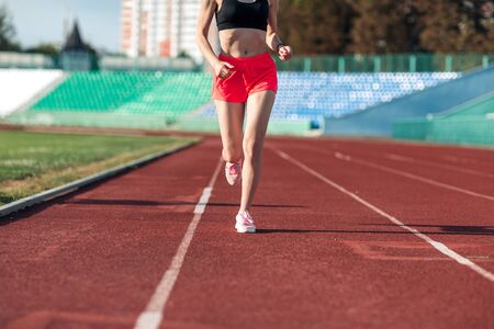 Sport. Woman fitness legs running on stadium. Close up of feet of a runner. Woman fitness jog workout wellness concept. Athlete runner feet running on running track