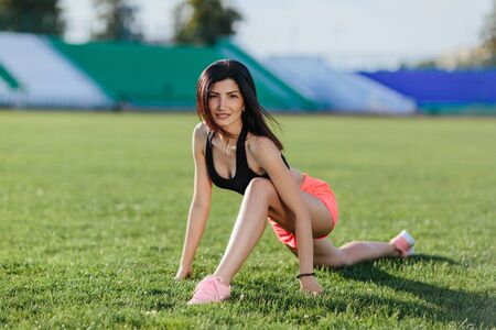 Young beautiful fitness girl doing stretching on the stadium. Summer sport activity. Green stadium grass on background.
