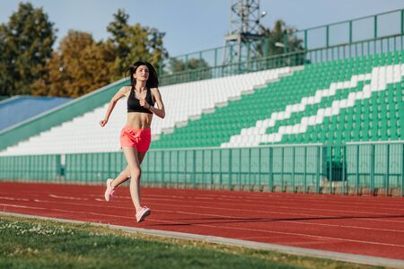 Young fitness brunette woman in shorts and top running on a stadium track. Athlete girl doing exercises on the training at stadium. Healthy active lifestyle