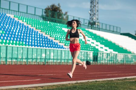 Sporty young brunette woman in pink shorts and tank top running at the stadium. Healthy active lifestyle. Summer sport activity