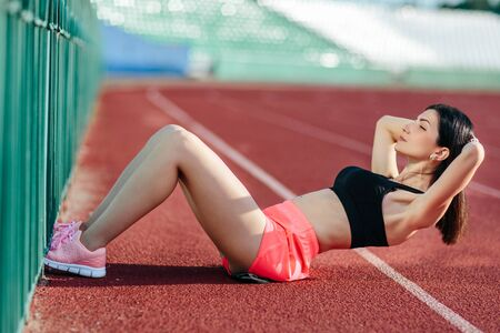 Beautiful sporty brunette woman in pink shorts and tank top appearance doing exercises on the stomach on the stadium track. Womens fitness. Sports training in the fresh air. Reklamní fotografie
