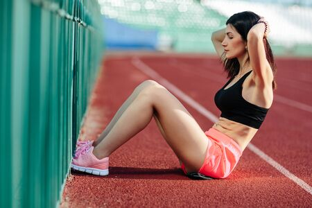 Beautiful brunette woman in pink shorts and tank top does exercises with press at the stadium.
