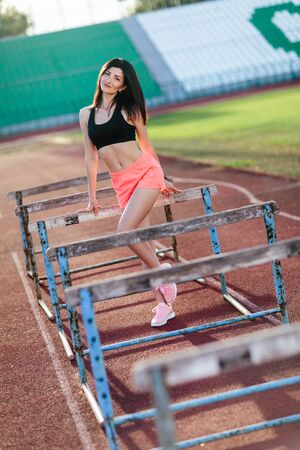 Young woman athlete on stadium sporty lifestyle standing on track posing to camera smiling playful Banco de Imagens