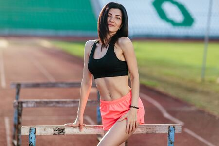 Stylish brunette woman in pink shorts and tank top posing for the camera on running track near the barriers running jumping at the stadium. Banco de Imagens