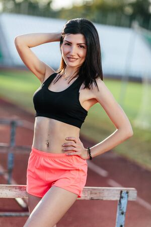 Portrait of young brunette woman athlete on stadium sporty lifestyle standing on track posing near the barriers running jumping to camera smiling playful.