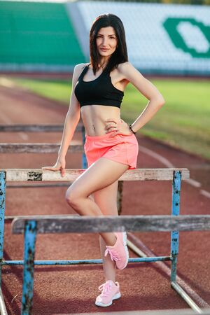 Young brunette woman athlete on stadium sporty lifestyle standing on track posing near the barriers running jumping to camera smiling playful.