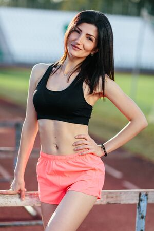 Young brunette woman athlete on stadium sporty lifestyle standing on track posing near the barriers running jumping to camera smiling playful Banco de Imagens