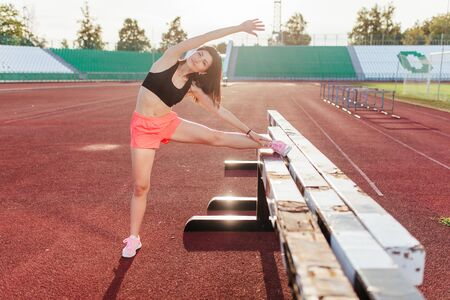 Beautiful brunette runner woman doing stretching leaning her leg on barrier for running stretching before workout - outdoor shot. Sport girl doing exercise in the stadium. Banco de Imagens