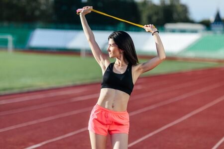 Young brunette woman athlete with a perfect figure on stadium sporty lifestyle standing on track stretching with jump rope.