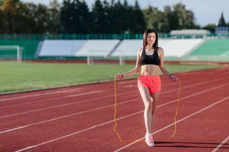 Full length view of young sportswoman exercising with skipping rope on stadium Banco de Imagens