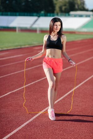 Woman with rope. Sport brunette woman posing with yellow rope, healthy activity. Sexy woman with skipping rope. Muscular woman on the Modern football stadium. Sport girl doing exercises on the stadium.