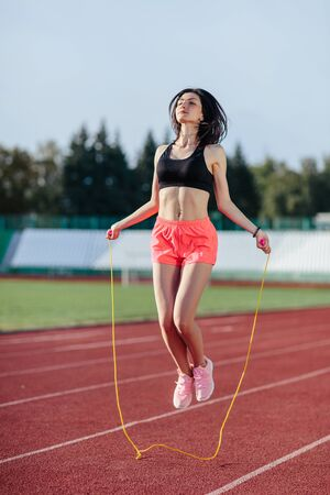 Achieving best results. Beautiful young woman in sports clothing skipping rope and smiling while exercising on the running track outdoors