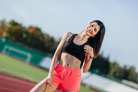 Achieving best results. Beautiful young brunette woman in sports clothing skipping rope and smiling while exercising on the running track outdoors. Banco de Imagens