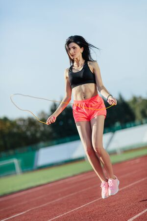 Sport, exercises outdoors. woman in black top and rose shorts jumping on skipping rope on stadium. Sporty girl in good shape, full body, outdoors. Banco de Imagens