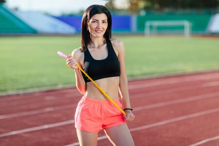 Image of happy young sports woman outdoors on grass holding skipping rope.