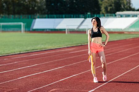 Happy young sports brunette woman in sportswear posing with yellow skipping rope on the stadium. Healthy active lifestyle.