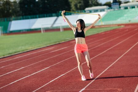 Portrait of happy young sports brunette woman in black top and rose shorts outdoors on stadium holding skipping rope.