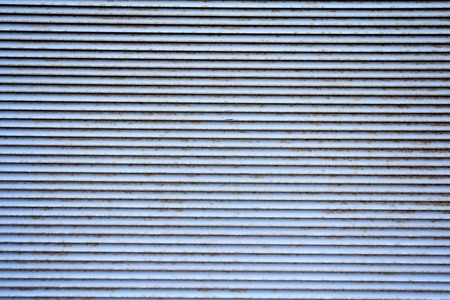 rolling garage door: old and damaged metal shutters with rust appearing