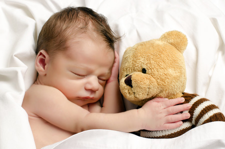 after bath: Beautiful innocent newborn sleeping. Adorable little boy relaxing in white sheets after a bath and holding close to him his bear toy
