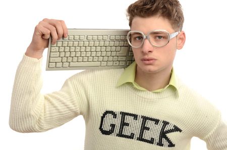 Geek playing video games with a keyboard, gamer wearing eyeglasses