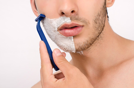 skin care: Shaving the beard with a razor. Young man shaving his beard in the morning with a razor