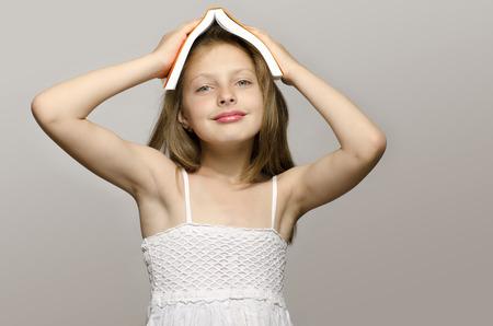 školačka: Holčička čtení některé knihy, dítě učení, dítě studuje, dítě baví s knihou. Dívka s knihou na hlavě s úsměvem a myšlení, příprava do školy