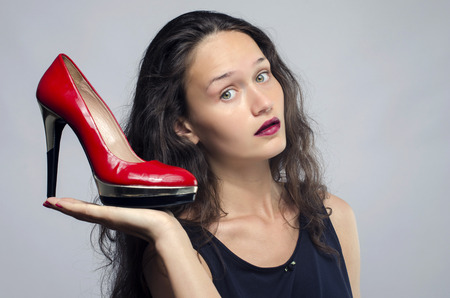 high heel shoes: Woman in love with her high heel shoes. Beautiful girl holding her red sexy stiletto shoe. Lady shopping for shoes