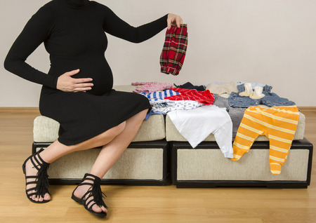 baby wardrobe: Pregnant woman looking at newborn clothes for her future baby, mother searching her new wardrobe for her infant Stock Photo