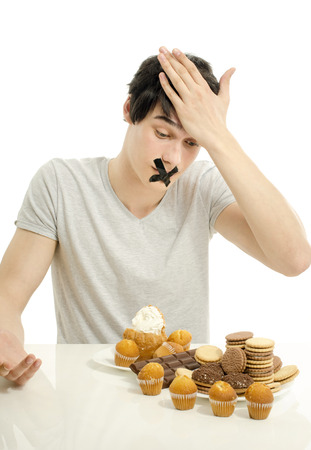 withhold: Man in love with sweets, candies,chocolate and sugar but trying to withhold. Forbidden sweets for a healthy longer life Stock Photo