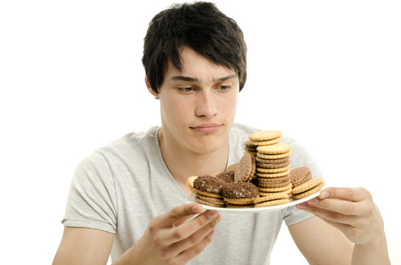 forbidden love: Man in love with sweets, candies,chocolate and sugar but trying to withhold. Forbidden sweets for a healthy longer life Stock Photo
