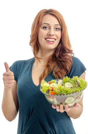 Happy woman eating salad. Woman keeping a diet with green salad and approving organic raw food