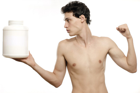 steroids: Skinny man training and drinking a protein shake. Anorexic young man training to become stronger and using steroids