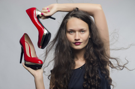 glamour shopping: Woman in love with her high heel shoes. Beautiful girl holding her red sexy stiletto shoe. Lady shopping for shoes