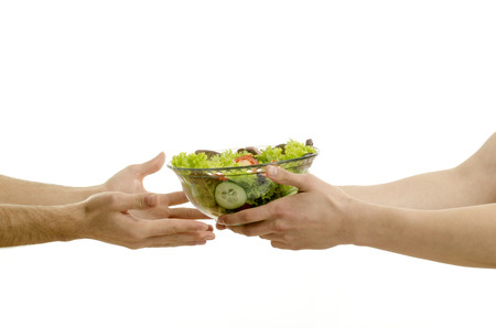 Hand offering a bowl of organic salad and other hands receiving isolated on white photo