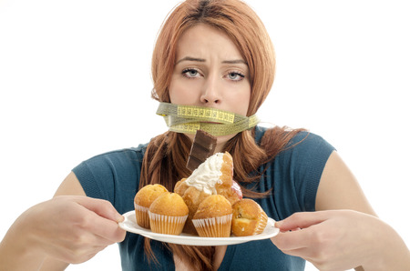 Woman with a centimeter on her mouth unable to eat all the sweets and sugar, lots of cookies on a plate. Dieting without sweets