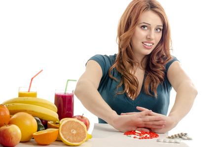pastillas: Paciente decir no a un tratamiento médico. Hermosa mujer se niega a tomar las píldoras y optar por comer frutas orgánicas crudas, ensaladas, batido, zumos para una vida saludable Foto de archivo