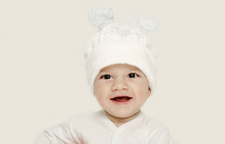 bunny ears: Innocent baby wearing a white hat looking adorable. Kid dressed for winter, lovely newborn. Adorable baby portrait looking curious.  Baby dressed as a funny bunny with a white hat with rabbit ears