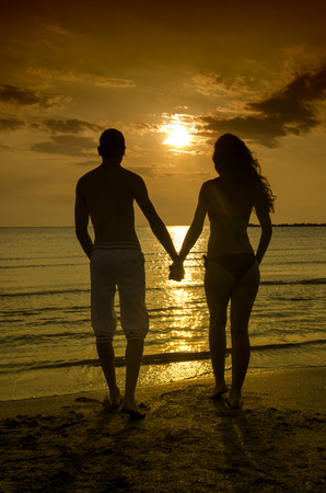 ビーチで日の出で自分の時間を楽しんでいるカップル、ロマンチックなシーンで手を繋いでいるカップル。2 人の恋人のシルエット