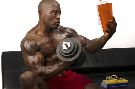 pecs: Bodybuilder training hard while reading a book. Strong man with perfect abs, pecs shoulders,biceps, triceps